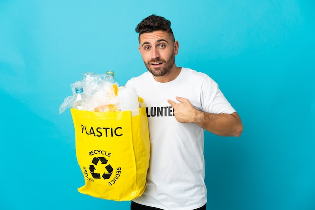 Kaukasischer mann, der eine tasche voller plastikflaschen hält, um lokalisiert auf blauem hintergrund mit überraschendem gesichtsausdruck zu recyceln