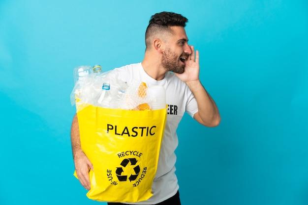 Kaukasischer mann, der eine tasche voller plastikflaschen zum recyceln hält, isoliert auf blauem hintergrund, der mit weit geöffnetem mund zur seite schreit