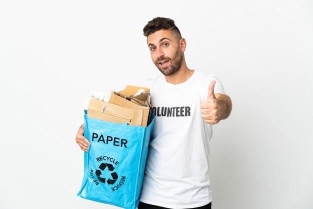 Kaukasischer mann, der einen recyclingbeutel voll papier hält, um isoliert auf weißem hintergrund mit daumen oben zu recyceln, weil etwas gutes passiert ist