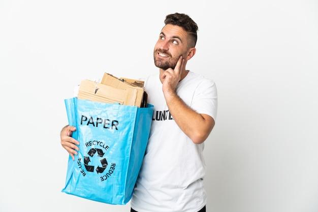 Kaukasischer mann, der einen recyclingbeutel voll papier hält, um lokalisiert auf weißem hintergrund zu denken, der eine idee beim nachschlagen denkt