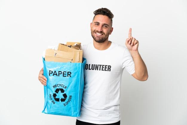 Kaukasischer mann, der einen recyclingbeutel voll papier hält, um lokalisiert auf weißem hintergrund zu recyceln, der eine große idee zeigt