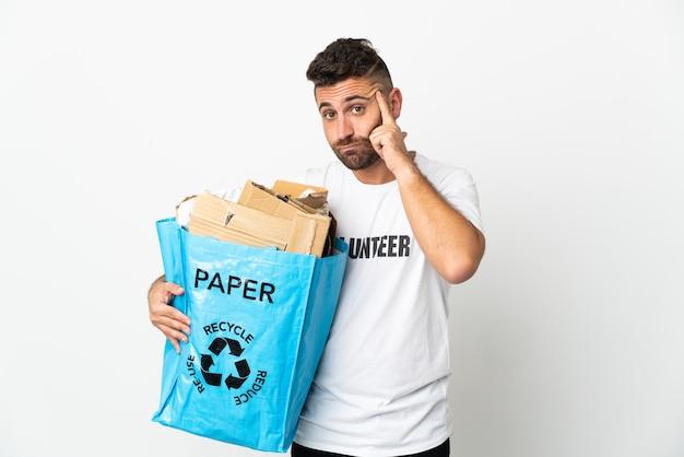 Kaukasischer mann, der einen recyclingbeutel voll papier hält, um lokalisiert auf weißer wand zu recyceln, die eine idee denkt