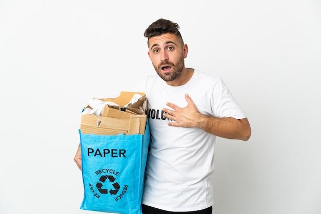 Kaukasischer mann, der einen recyclingbeutel voller papier hält, um isoliert auf weiß zu recyceln, überrascht und schockiert, während er richtig schaut