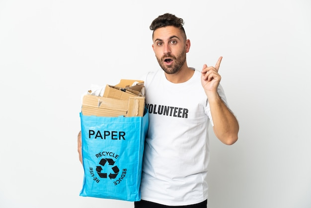 Kaukasischer mann, der einen recyclingbeutel voller papier hält, um isoliert auf weiß zu recyceln, um die lösung zu realisieren, während ein finger angehoben wird