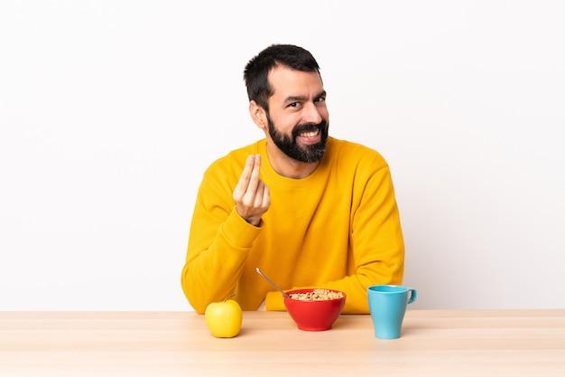 Kaukasischer mann, der frühstück in einer tabelle macht, die geldgeste macht