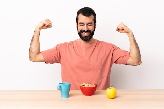 Kaukasischer mann, der frühstück in einer tabelle tut, die starke geste tut.