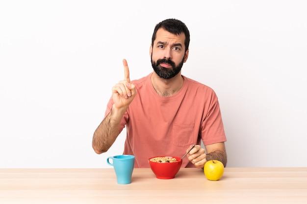 Kaukasischer mann, der frühstück in einer tabelle zählt, die eins mit ernstem ausdruck zählt.