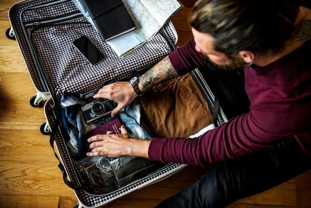 Kaukasischer mann, der gepäck für eine reise packt