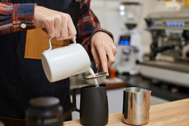 Kaukasischer mann, der heiße milch in kaffee gießt