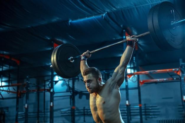 Kaukasischer mann, der im fitnessstudio gewichtheben übt. kaukasisches männliches sportliches modelltraining mit langhantel, sieht selbstbewusst und stark aus. bodybuilding, gesunder lebensstil, bewegung, aktivität, aktionskonzept.