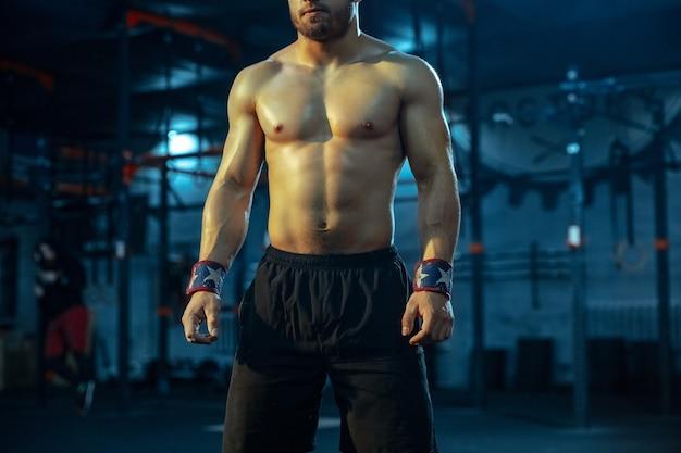 Kaukasischer mann, der im fitnessstudio gewichtheben übt