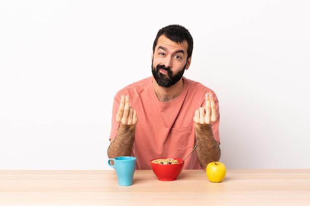 Kaukasischer mann, der in einem tisch frühstückt, der geldgestik macht, aber ruiniert ist
