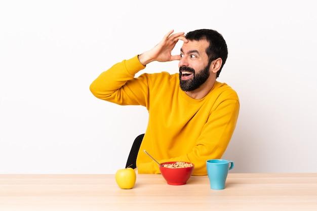 Kaukasischer mann, der in einem tisch mit überraschungsausdruck frühstückt, während er seitlich schaut.