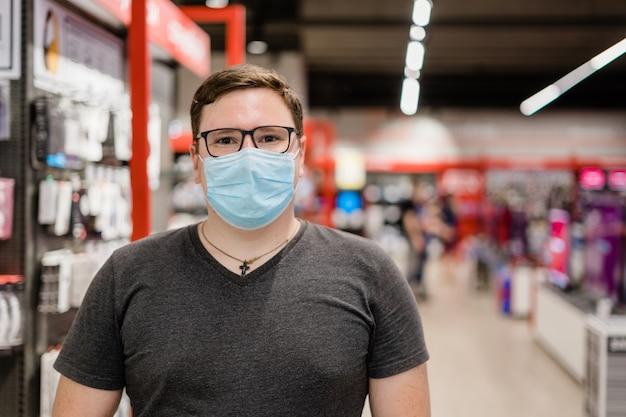Kaukasischer mann, der kleidung mit medizinischer maske einkauft. neues normales konzept.