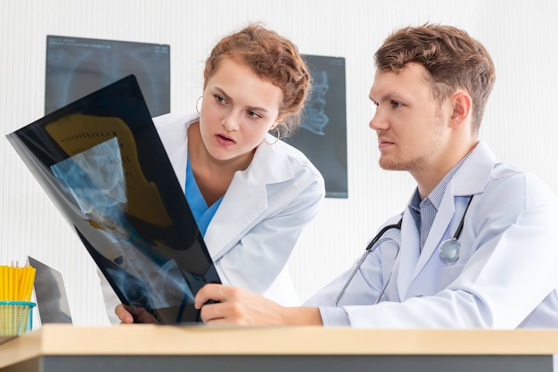 Kaukasischer mann der medizinischen fachkräfte, der röntgenbild und gespräch über patient mit junger ärztin hält. gestresster und besorgter arzt gibt schlechte nachrichten.