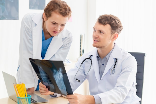 Kaukasischer mann der medizinischen fachkräfte, der röntgenbild und gespräch über patient mit junger ärztin hält.