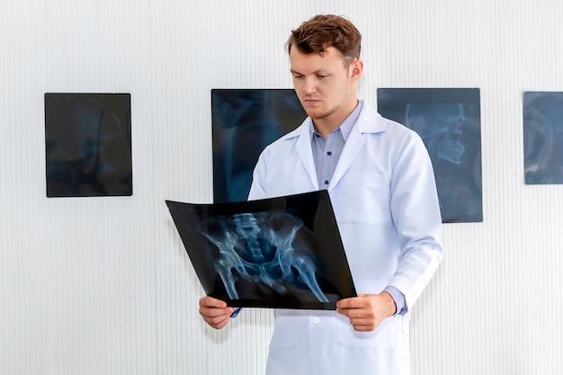 Kaukasischer mann der medizinischen fachkräfte, der röntgenstrahl im hopitalraum hält.