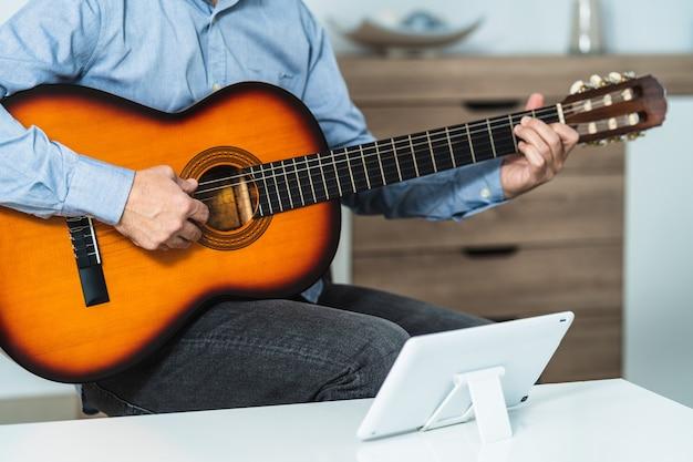 Kaukasischer mann, der online-spanisch-gitarrenunterricht mit dem tablet erhält