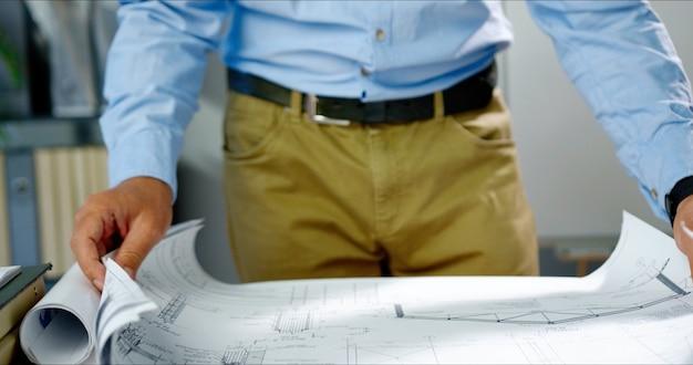 Kaukasischer mann, der papier mit großem zeichenplan auf tisch ausrollt und es untersucht. männlicher ingenieur, der im büro arbeitet. architector mit entwurf. innen.
