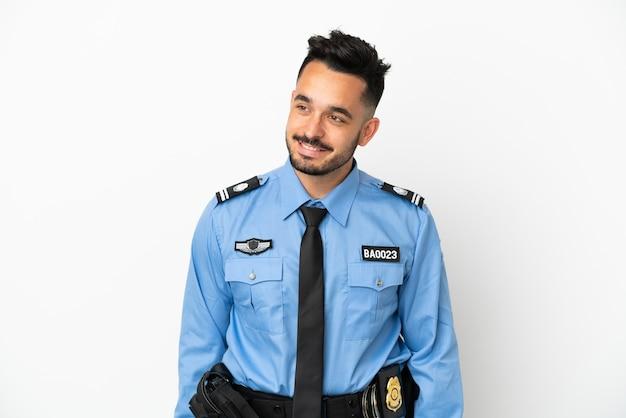 Kaukasischer mann der polizei isoliert auf weißem hintergrund, der zur seite schaut und lächelt