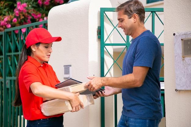 Kaukasischer mann, der seine bestellung von der lieferfrau erhält. lateinischer kurier liefert bestellung, hält pakete und zwischenablage, trägt rote mütze und hemd. express-lieferservice und online-shopping-konzept