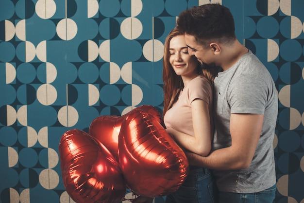 Kaukasischer mann, der seine frau umarmt und ihr luftballons auf einem datum gibt, das zusammen lächelt