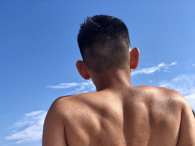 Kaukasischer mann, der sich unter der warmen sonne mit dem blauen himmel entspannt