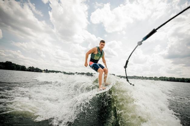 Kaukasischer mann, der stilvolles wakeboard reitet