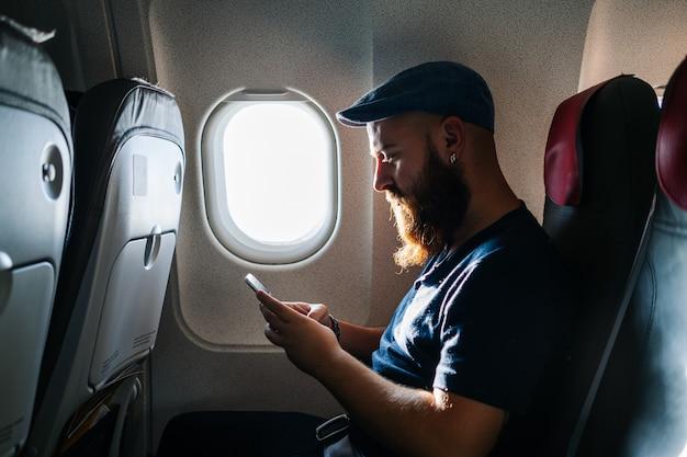 Kaukasischer mann, der telefon in das flugzeug verwendet