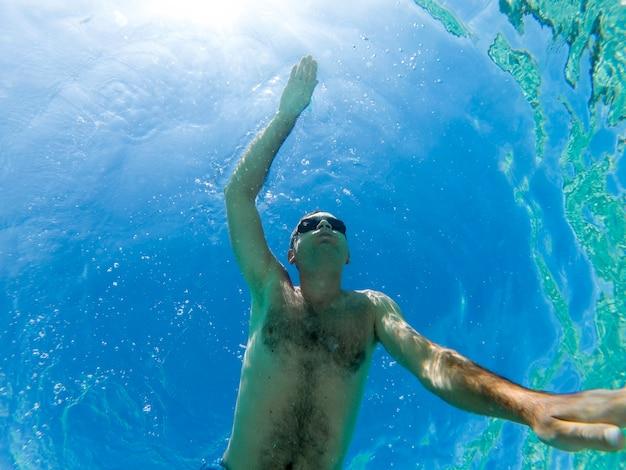 Kaukasischer mann, der unter dem wasser im blauen transparenten wasser der schwimmbrille schwimmt