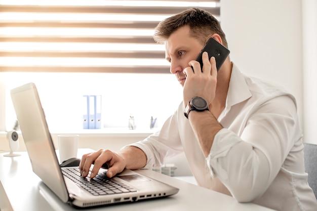 Kaukasischer mann, der vom hauptbüro arbeitet und am telefon spricht