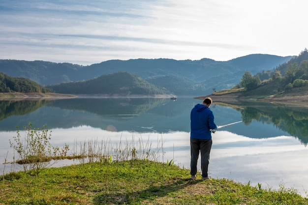 Kaukasischer mann, der von einem schönen ruhigen see fischt, umgeben von grünen hügeln bei tageslicht surrounded
