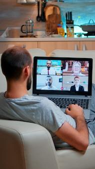 Kaukasischer mann, der während der videoanrufkonferenz mit kollegen spricht
