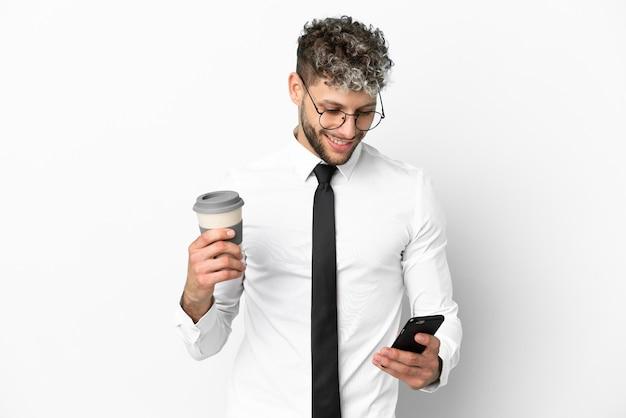 Kaukasischer mann des geschäfts lokalisiert auf weißem hintergrund, der kaffee zum mitnehmen und ein handy hält