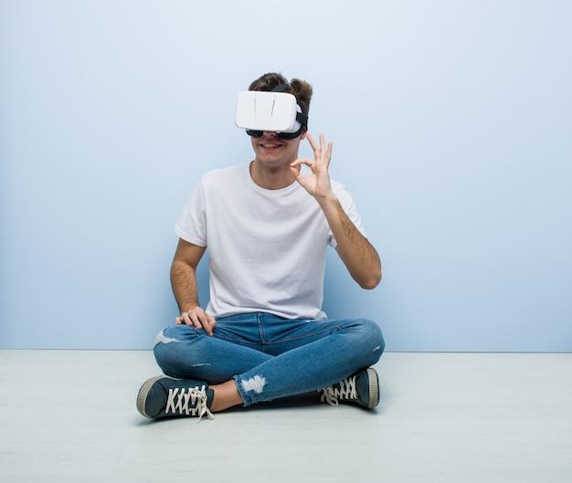 Kaukasischer mann des jugendlichen, der die gläser einer virtuellen realität sitzen auf dem boden verwendet