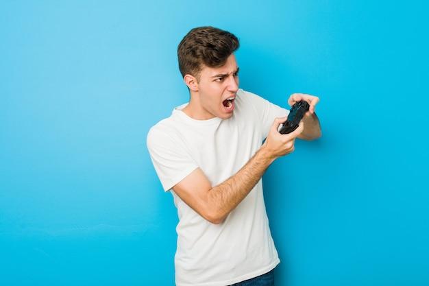 Kaukasischer mann des jugendlichen, der einen gamecontroller verwendet