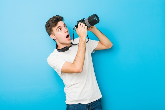 Kaukasischer mann des jugendlichen, der fotos mit einer spiegelreflexkamera macht