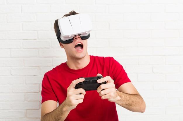 Kaukasischer mann des jugendlichen, der gläser der virtuellen realität und gamecontroller verwendet