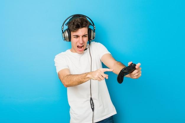 Kaukasischer mann des jugendlichen, der kopfhörer und gamecontroller verwendet