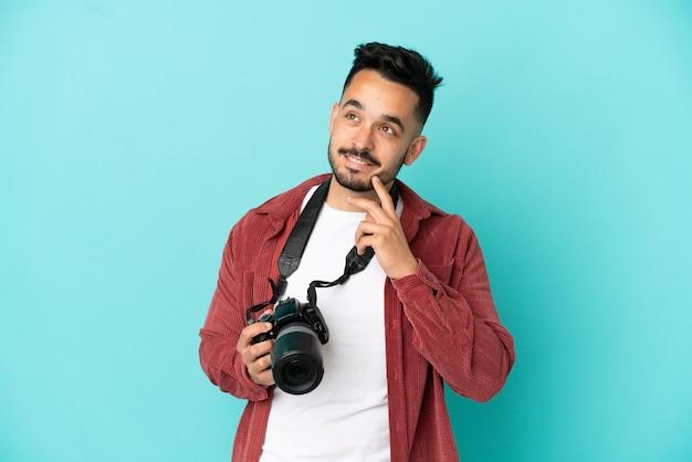 Kaukasischer mann des jungen fotografen isoliert auf blauem hintergrund, der beim nachschlagen eine idee denkt