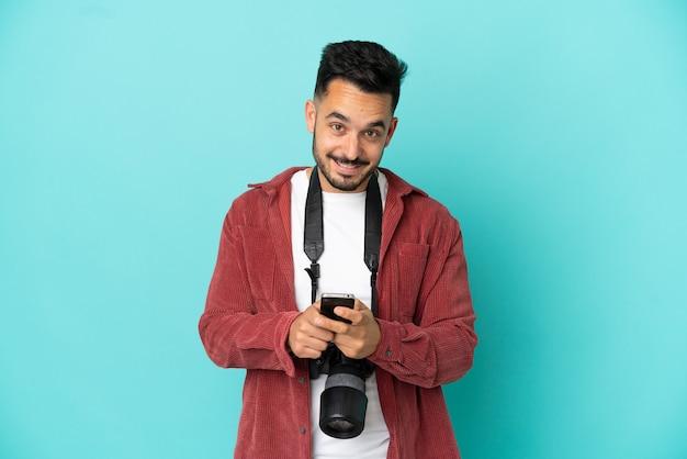 Kaukasischer mann des jungen fotografen lokalisiert auf blauem hintergrund, der eine nachricht mit dem handy sendet