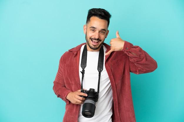 Kaukasischer mann des jungen fotografen lokalisiert auf blauem hintergrund, der telefongeste macht. ruf mich zurück zeichen