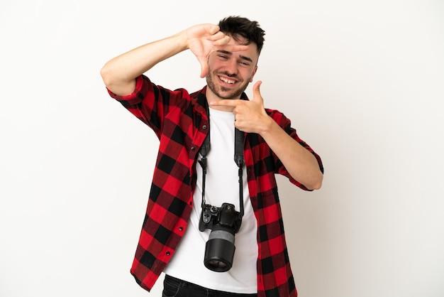 Kaukasischer mann des jungen fotografen lokalisiert auf dem fokusgesicht des weißen hintergrundes. rahmensymbol