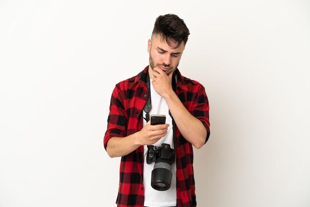 Kaukasischer mann des jungen fotografen lokalisiert auf weißem hintergrund, der eine nachricht denkt und sendet