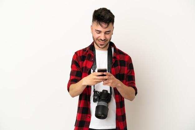 Kaukasischer mann des jungen fotografen lokalisiert auf weißem hintergrund, der eine nachricht mit dem handy sendet