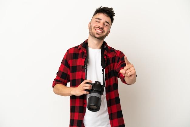 Kaukasischer mann des jungen fotografen lokalisiert auf weißem hintergrund, der einen finger zeigt und anhebt
