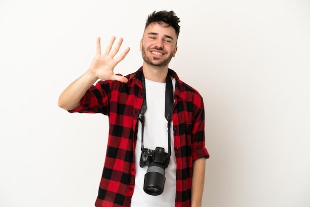 Kaukasischer mann des jungen fotografen lokalisiert auf weißem hintergrund, der fünf mit den fingern zählt