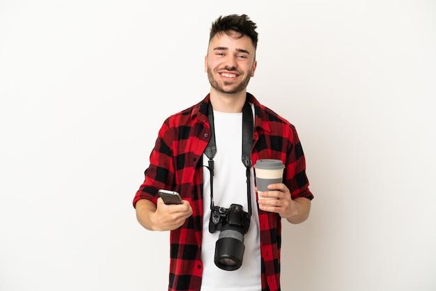 Kaukasischer mann des jungen fotografen lokalisiert auf weißem hintergrund, der kaffee zum mitnehmen und ein handy hält