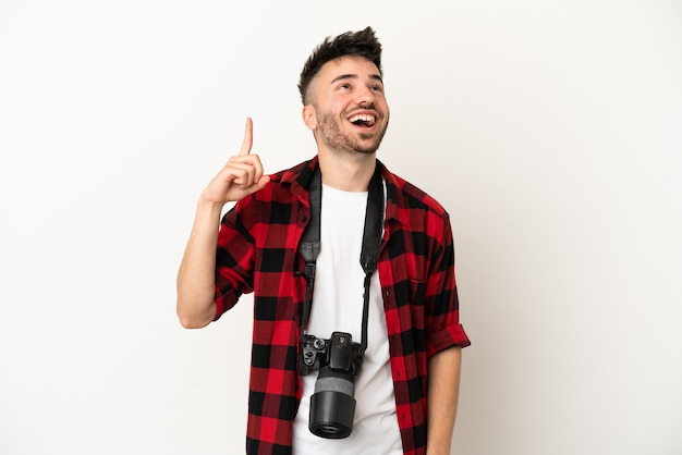 Kaukasischer mann des jungen fotografen lokalisiert auf weißem hintergrund, der nach oben zeigt und überrascht