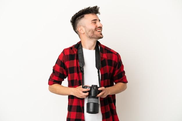 Kaukasischer mann des jungen fotografen lokalisiert auf weißem hintergrund glücklich und lächelnd